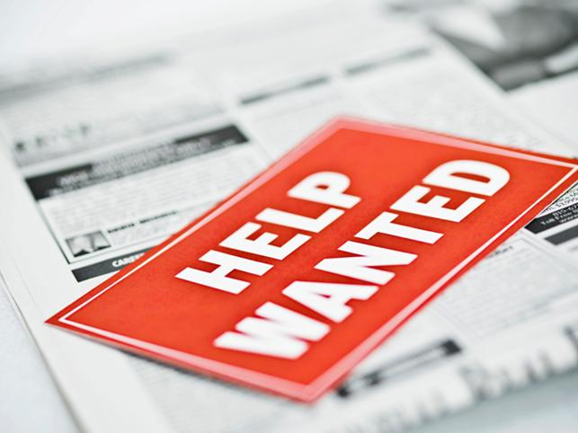 help wanted sign on newspaper